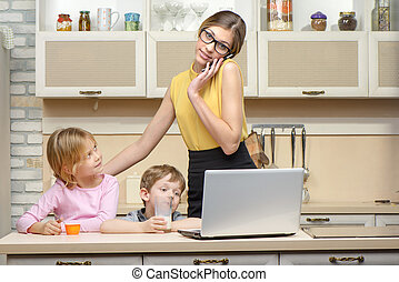 Young business woman havining breakfast with her little children