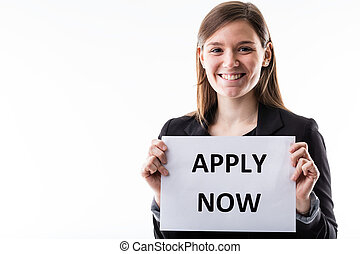young business woman holding an apply now sign