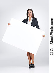 Young business woman holding big blank poster. Standing isolated on white