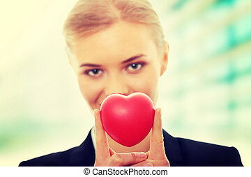 Young business woman holding heart
