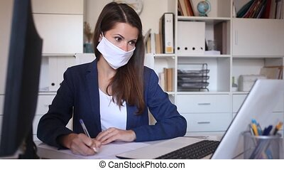 Young business woman holding meeting in office in medical face mask to prevent spread of viral infection
