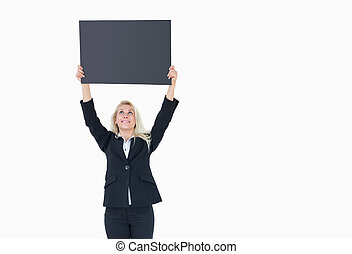 Young business woman holding up empty banner