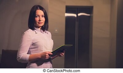 Young business woman hotel manager in an elevator with a Tablet PC