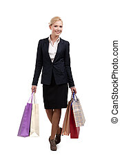 Young business woman in a black suit holding shopping bags, full length