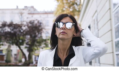 Young business woman in the glasses goes around the city