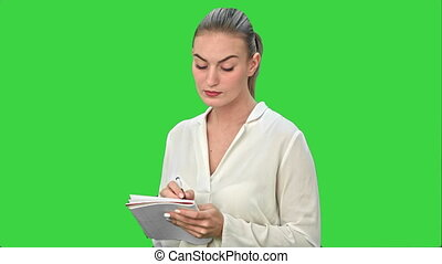 Young business woman inventing ideas, writing the, down to the notebook on a Green Screen, Chroma Key.