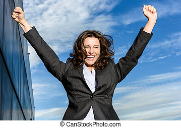 Young Business Woman is jumping for joy in front of blue ...