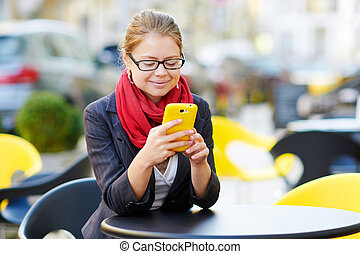 Young business woman is using smart phone for work in cafe