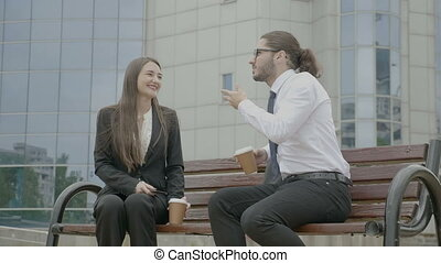 Young business woman listening to her businessman colleague...