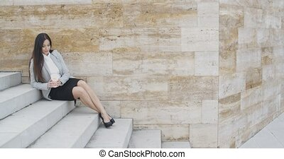 Young business woman on stairs drinking coffee