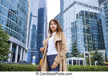 Young business woman on the background of skyscrapers