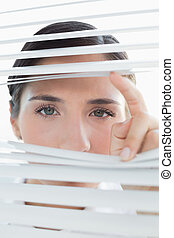 Young business woman peeking through blinds - Close-up ...