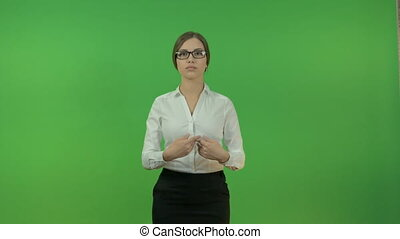 Young business woman raising her hands in different directions on a green background.