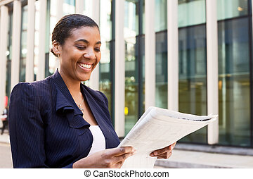 young business woman reading the newspaper