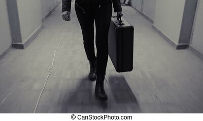 Young business woman runs away with suitcase.
