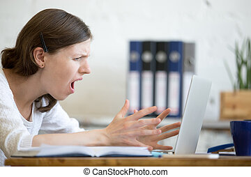 Young business woman screaming at laptop