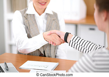 Young business woman shaking hands with a client at the office. Successful insurance business concept .