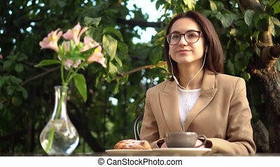 Young business woman sits in a cafe and listens to music through headphones. Girl with coffee and a bun on the summer veranda. 4k