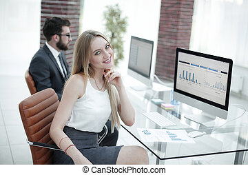 young business woman sitting at the desk together with a colleague.