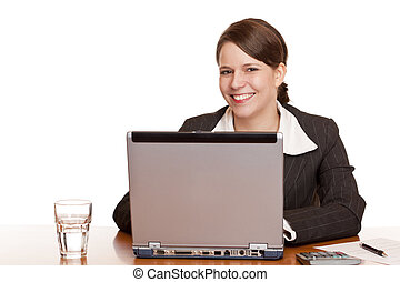 Young business woman sitting happy in office and works on computer