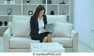 Young business woman sitting on the couch with a notebook in...