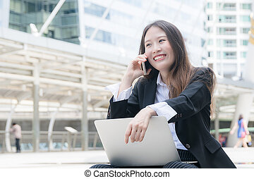 Young business woman smiling working with laptop out door, looking screen With gesture of happy rejoicing, shock, surprise emotion
