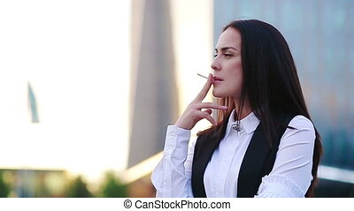 Young business woman smoking and looking stressed