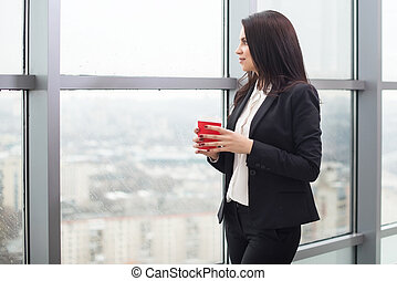 Young business woman standing at window with cup of coffee