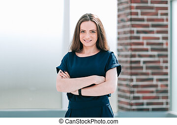 young business woman standing in office lobby