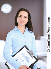 Young business woman standing in office