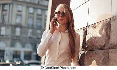 Young business woman standing near office building at the sunny city streets and talking on a mobile cell phone. Attractive happy girl with sunglasses using cellphone outdoors, sunset