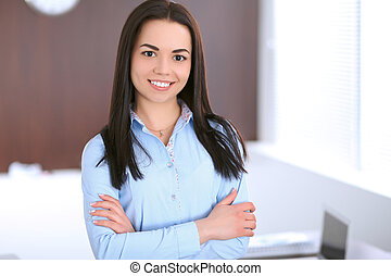 Young business woman standing with crossed arms  in office