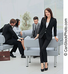 Young business woman standing with her collegues in background a
