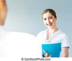 Young business woman talking with a colleague, interviews