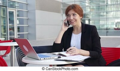 Young business woman talking by smartphone