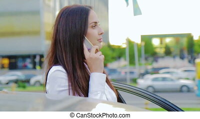 Young business woman talking on a phone next to her car