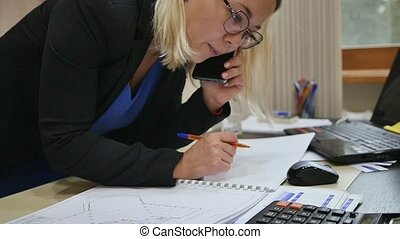 Young business woman talking on the phone in the office, examining blueprints on the table