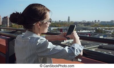 Young business woman texting message on the bascony.