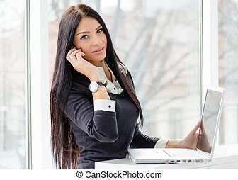 young business woman using laptop PC relaxed near window at...