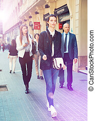 Young business woman walking on street