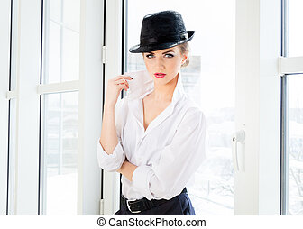 Young business woman wearing man's shirt, hat in office