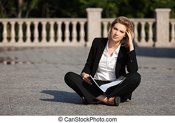 Young business woman with a folder sitting on the sidewalk