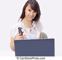young business woman with a pair of pliers sitting in front of an open laptop