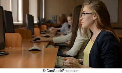 Young business woman with glasses working at computer. A...