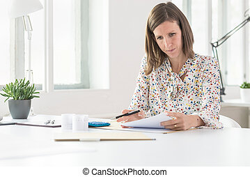 Young business woman working at her office desk with documents