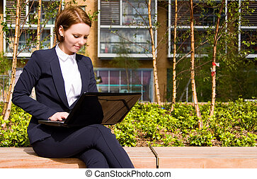 Young business woman working on laptop outdoors.