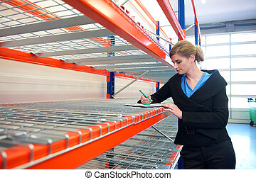 Young business woman writing on clipboard in warehouse