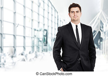 A portrait of a young businessman standing over the background of his modern office