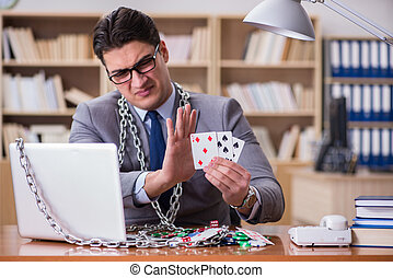 Young businessman addicted to online gambling cards playing in t