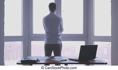 Young businessman admire view from the window spreads his...